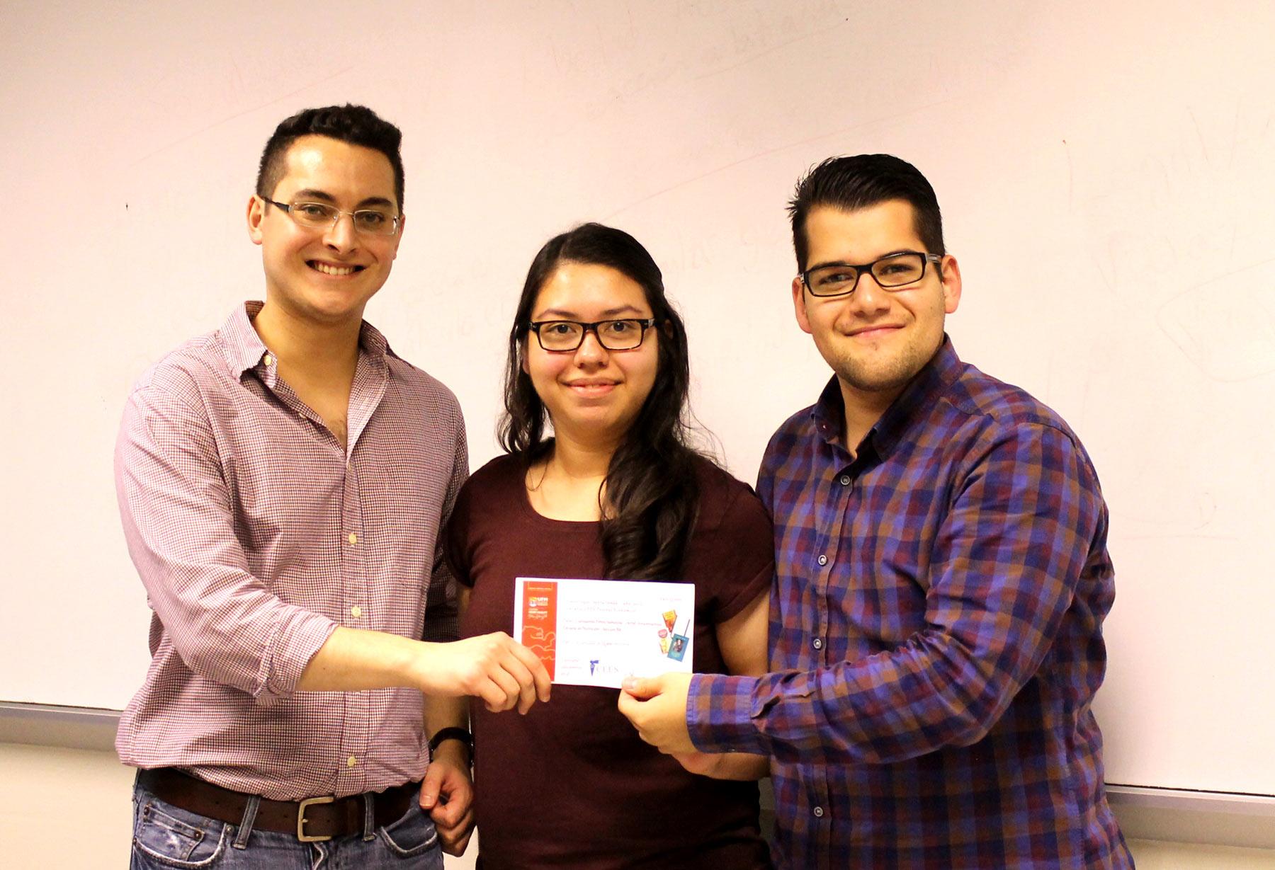 Los profesores Edgar Ortiz y Elder Flores le entregan el premio a Carolianne Pérez.  (Foto por Centro Henry Hazlitt)